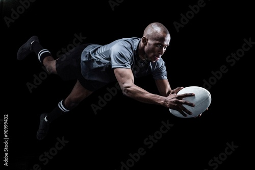 Fotografiet  Sportsman jumping for catching rugby ball