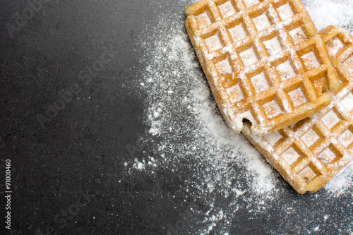 Fotomural  Waffles with sugar on slate table