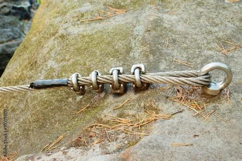 Foto op Plexiglas Alpinisme Mountain wall with carabine in the sandstone rock. End of the steel rope in loop.