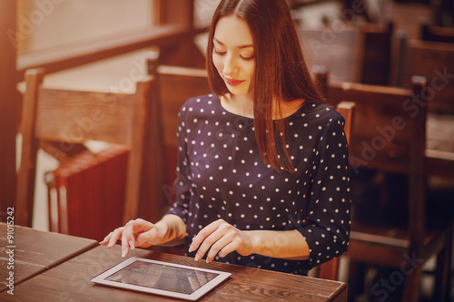 Poster de jardin Bar beautiful young girl enjoys phone and tablet