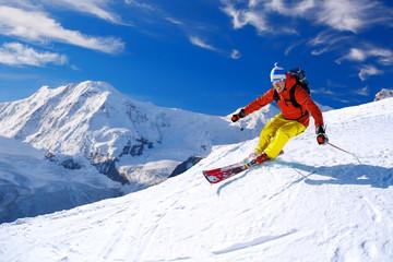 Skijaš skijajući nizbrdo u visokim planinama nasuprot plavom nebu