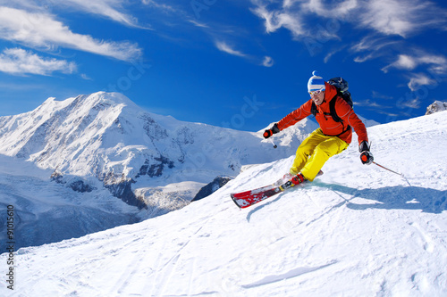 Poster Glisse hiver Skier skiing downhill in high mountains against blue sky
