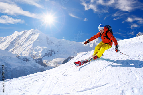 Tuinposter Wintersporten Skier skiing downhill in high mountains against blue sky