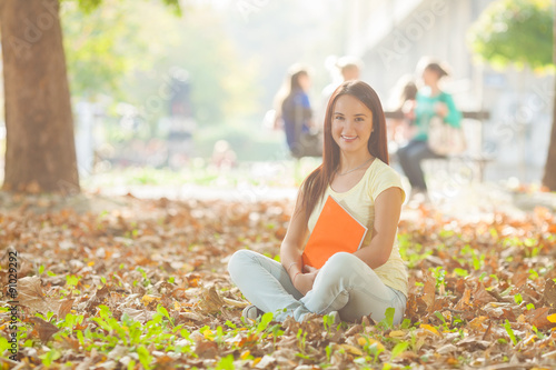 Fotografering  Portrait of beautiful college student sitting on the ground in a university camp
