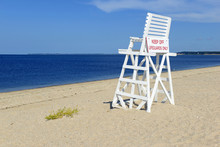 White Lifeguard Chair On Empty Sand Beach With Blue Sky