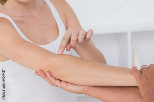Foto  Doctor stretching a young woman arm