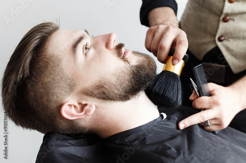 Barber cleaning face of his brutal customer with brush - 91051664