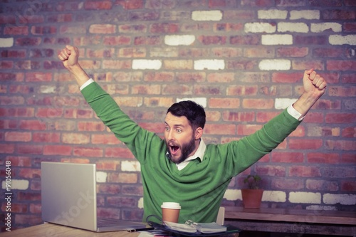 Happy businessman cheering while looking at laptop
