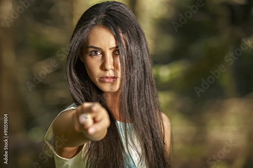 Closeup portrait of young angry woman pointing at someone as if Wallpaper Mural