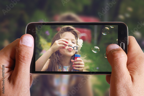Obraz Male hand taking photo of Vintage Portrait of beautiful girl blowing bubbles with cell, mobile phone. Kids, childhood, family concept. - fototapety do salonu
