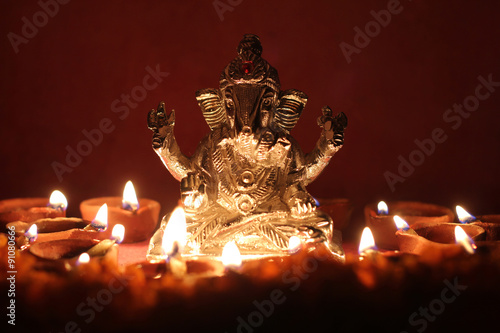 Ganesh idol surrounding with oil lamp, festival season