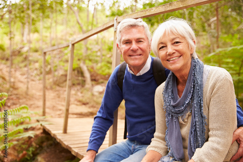Fotografía  Happy senior couple sitting on a bridge in forest, portrait