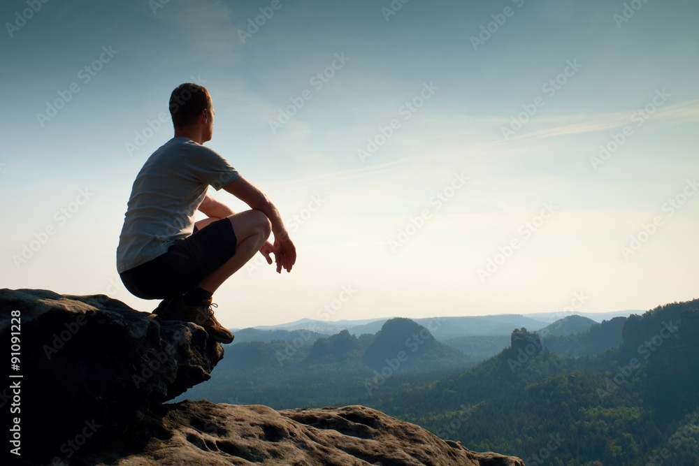 Fototapeta Young man in black sports pants and grey shirt  is sitting on cliff's edge and looking to misty valley bellow