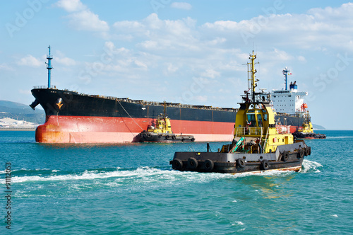 Photo Tanker barge pushed powerful tugboats in sea