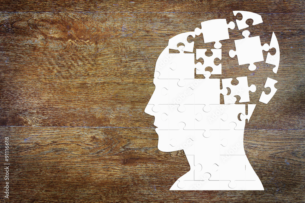 Fototapeta Human head as a set of puzzles on the wooden background