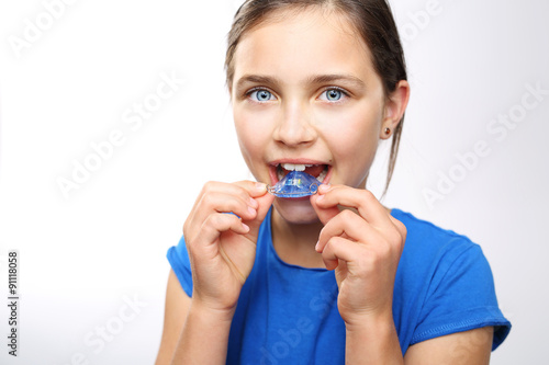 Dziewczynka zakłada aparat ortodontyczny na zęby