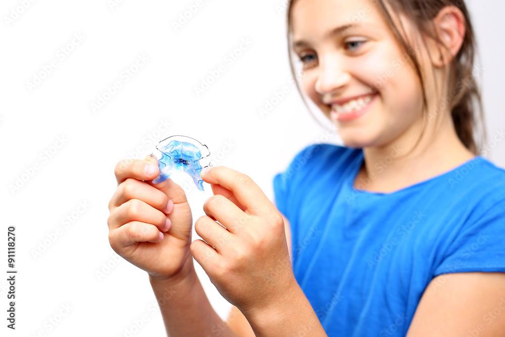 Fototapeta Ortodoncja.Dziewczynka z kolorowym aparatem ortodontycznym