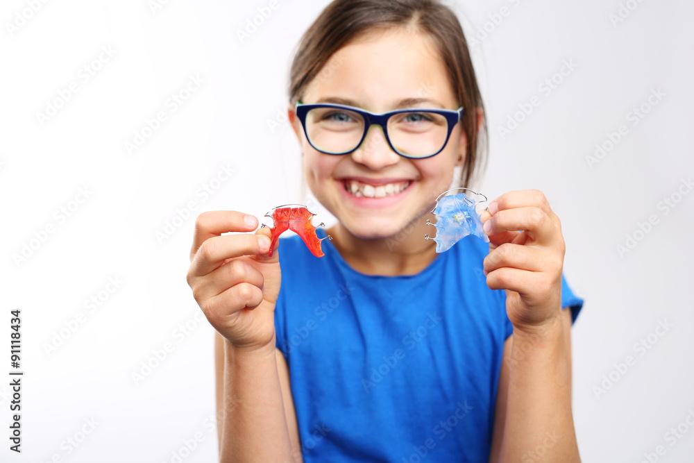 Fototapeta Zdrowy, piękny uśmiech, dziecko z aparatem ortodontycznym .Dziewczynka z kolorowym aparatem ortodontycznym