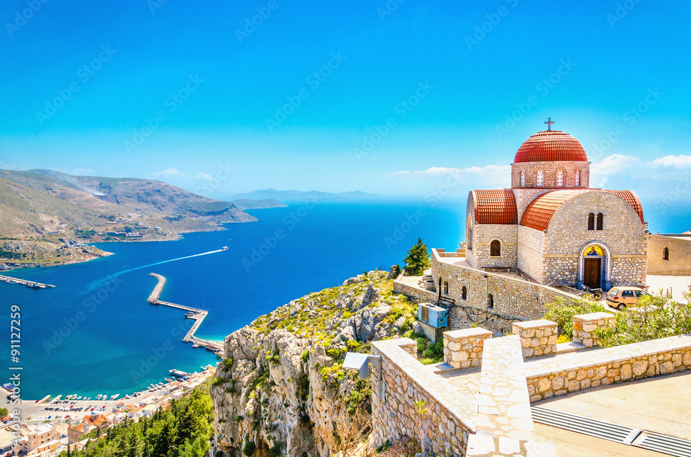 Fototapeta Remote church with red roofing on cliff, Greece