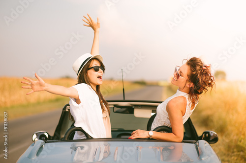Fotografia  Two happy female friends enjoying road trip in their cabriolet