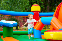 Happy Excited Boy Having Fun On Inflatable Attraction Playground