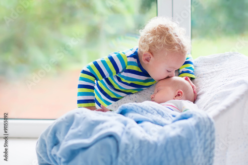 Valokuva  Little boy kissing newborn baby brother