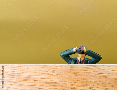 Fotografie, Obraz  Male Model with Binoculars Spies over a Wooden Wall