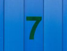 The Number Seven, Green, Set Against Blue Wood