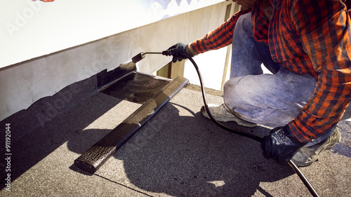 Roofer installing a roll of roofing felt by gas blowpipe torch Canvas Print