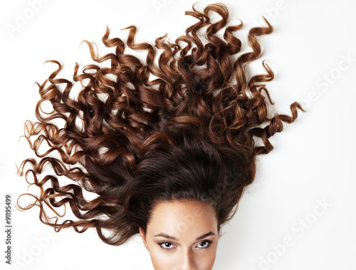 curly hair and part of woman's face, looking at the camera Canvas Print