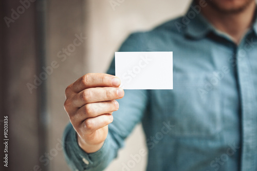 Fotografering  Man holding white business card on concrete wall background