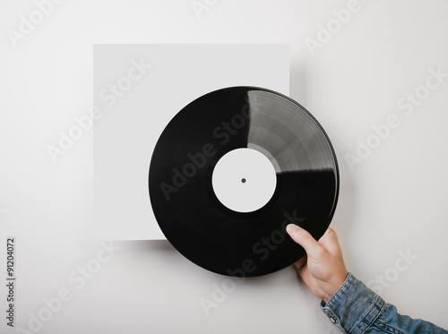 Male hand holding vinyl music album template on white wall backg male hand holding vinyl music album template on white wall backg maxwellsz