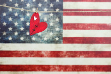 Wooden Heart Hanging In Front Of Blurred American Flag
