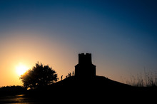 Sunset Silhouettes Of A Medieval Church On A Hill, Tree And Peop