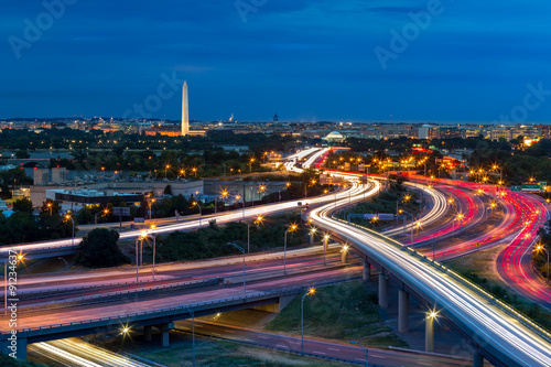 Cadres-photo bureau Autoroute nuit Washington D.C. cityscape at dusk with rush hour traffic trails on I-395 highway. Washington Monument, illuminated, dominates the skyline.