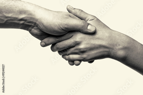 Black and white toned photo with two hands (helping hand to a friend)