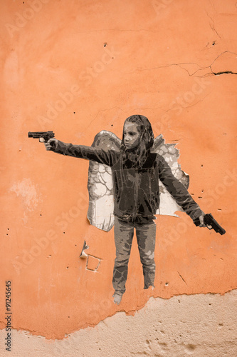 graffiti of child gangster on orange wall