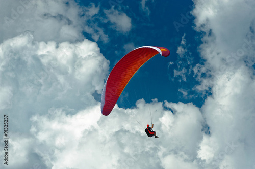 In de dag Luchtsport A paraglider gliding over the clouds