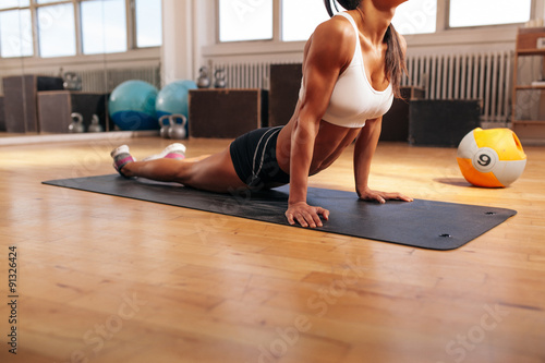 Photo  Muscular female doing stretching exercise in gym