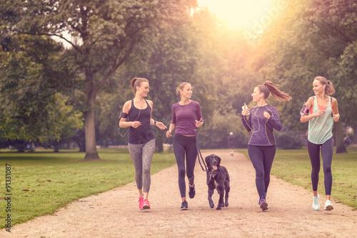 La pose en embrasure Jogging Gesundheitsbewusste Frauen laufen im Park mit ihrem Hund