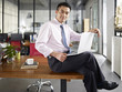 asian businessman sitting on desk with laptop computer in hand in office
