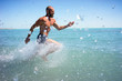 Bald middle-aged man quickly ran over the ocean with a naked torso