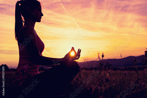 Fotografia  Young athletic woman practicing yoga on a meadow at sunset, silhouette
