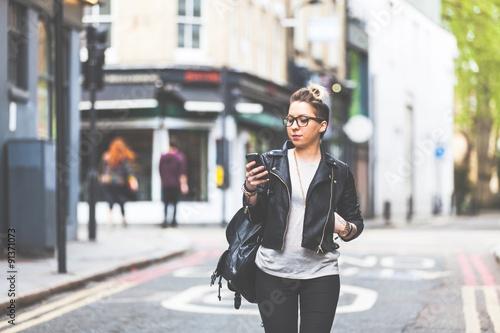 Fotografie, Obraz  Girl walking down the street with her phone.