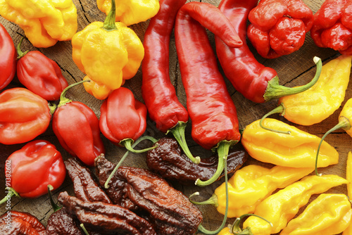 Poster Hot chili peppers Various hot peppers viewed from the top on a wooden background.