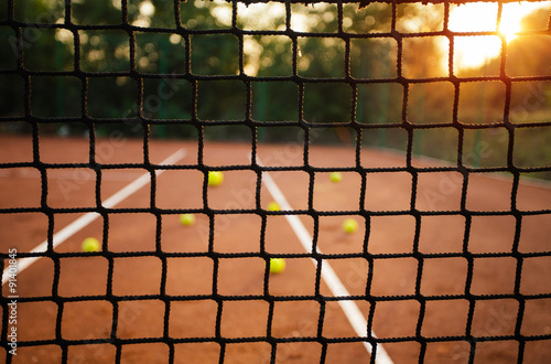 Close up of tennis net with balls in background - 91401845