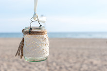 Glass Lantern Decorated With White Lace Hanging On Wedding