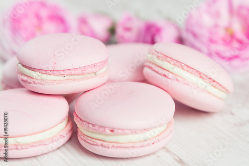 Gentle pink macaroons with rose on wood