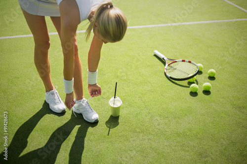 Tennis player tying shoes on the court Canvas Print