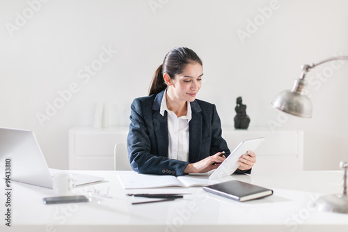 Garden Poster Portrait of a smiling businesswoman with dark hair sitting at he